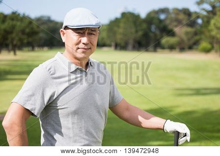 Thoughtful young man with golf club while standing on field