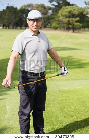 Portrait of golfer holding his golf club on field