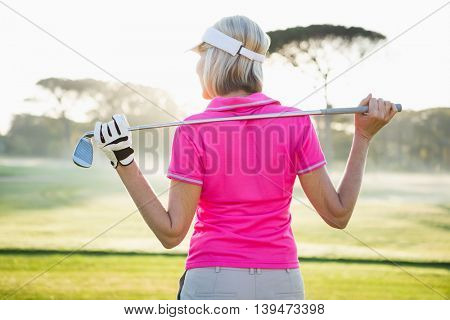 Rear view of woman golfer holding her club on field