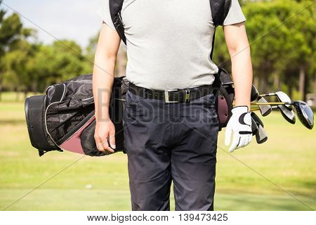 Midsection of man wearing golf bag while standing on field