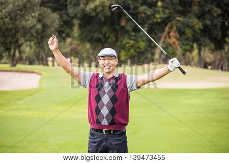 Golfer raising his arms on a field