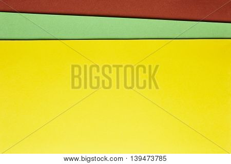 Colored cardboards background in yellow green brown tone. Copy space. Horizontal