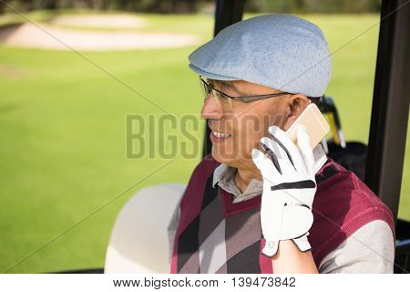 Profile view of golfer smiling and calling in his golf buggy