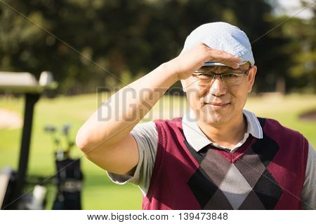 Golfer looking at camera with his hand on his cap