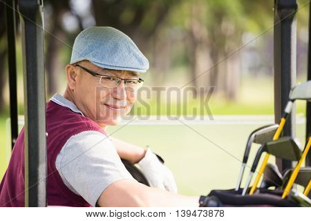 Golfer smiling and posing in his golf buggy
