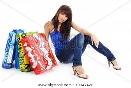 Closeup of young attractive woman smiling on surprise in the colorful shopping bags