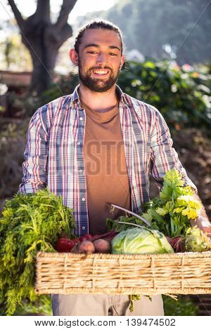 Happy young hipster gardener holding fresh organic vegetables at garden