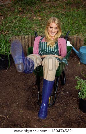 Portrait of happy young female gardener sitting in wheelbarrow at garden