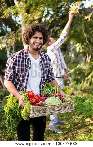 Portrait of happy young hipster gardener with fresh organic vegetables and colleague at garden