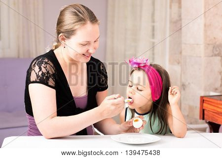 Mother and Daughter Are Eating Egg And Enjoy Being Together