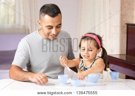 Little Girl is Serving Tea To Her Father With Her Toys