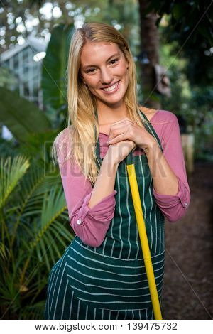 Portrait of attractive young female gardener with hand tool at garden