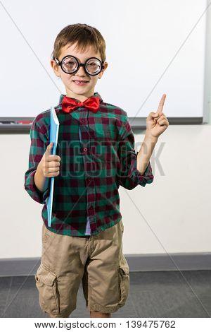 Portrait of cute boy raising hand against whiteboard in classroom