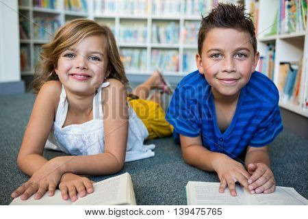 Portrait of girl and boy lying while reading books at library in school