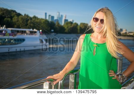 Smiling woman in sunglasses stands on ship deck during sailing in city