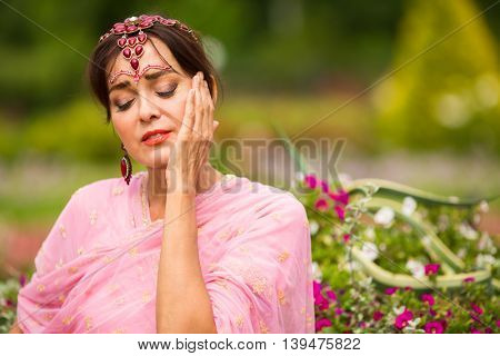 Middle age woman in pink sari and Indian adornment enjoying in summer park