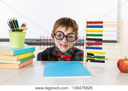Portrait of boy with books and abacus in classroom