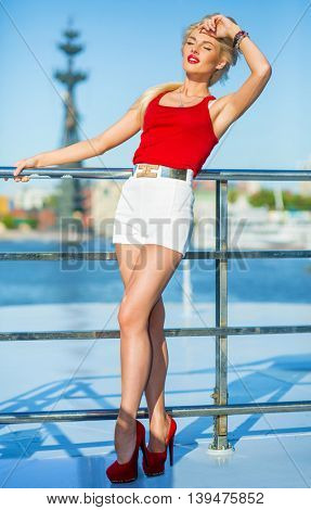 Blonde pretty woman poses on deck of ship at river at summer day