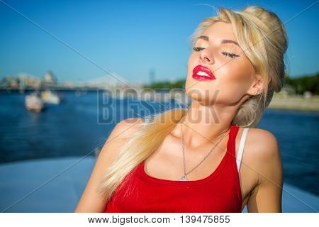 Beautiful woman poses near railing at deck of ship at river in summer city