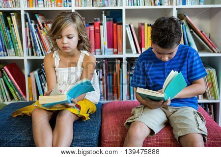 Elementary students reading books while sitting on seats in school library
