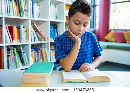 Elementary boy reading book at table in school library