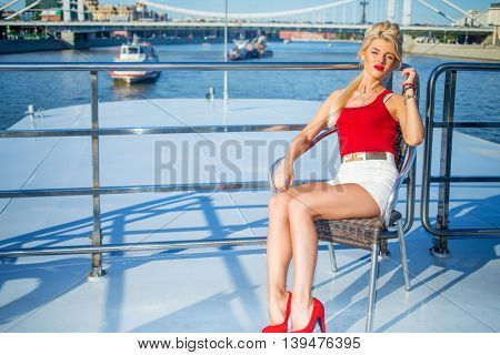 Beautiful blonde woman sits on chair on deck of ship at river in summer city