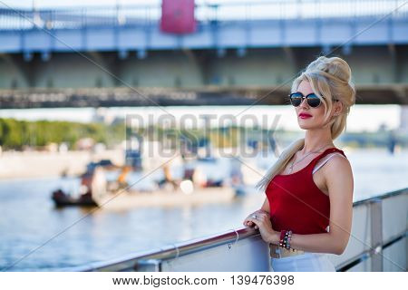 Blonde woman in sunglasses stands on ship deck during sailing in city