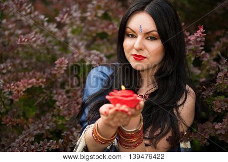 Brunette in blue sari among barberry bushes holding red burning candle in form of roses in hands