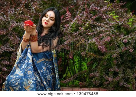 Brunette in sari among barberry bushes holding red burning candle in form of roses in hands