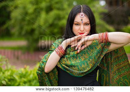 Brunette young woman in sari and Indian adornment poses in park