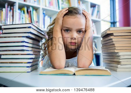 Portrait of stressed girl with books at table in school library