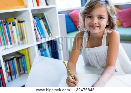 High angle portrait of smiling girl studying in school library