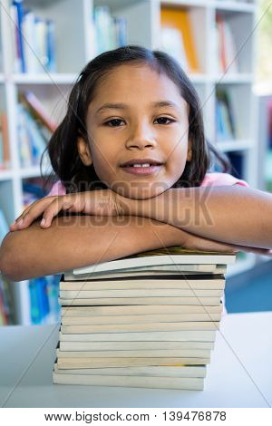 Portrait of smiling girl leaning on books at table in school library