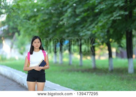 Girl female teenager with black hair in a bob white east Asian woman green park with a backpack background. Lady walking goes walk away look at the camera.