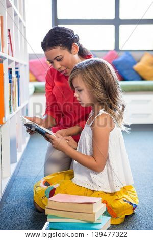 Young teacher assisting girl searching book in school library