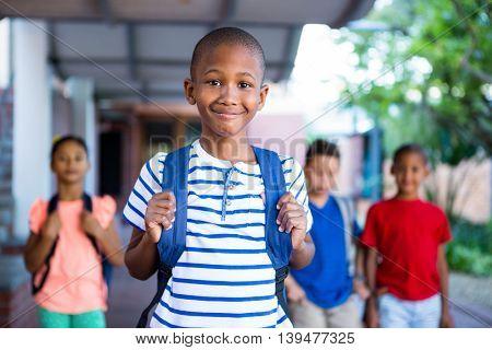 Portrait of schoolboy with classmates in background at school corridor