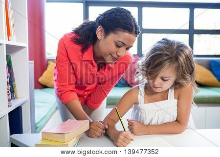 Young teacher assisting girl writing on notebook in school library