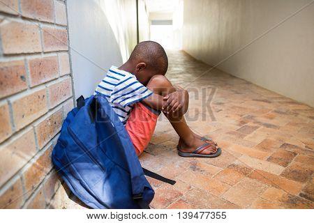 Boy sitting alone on corridor in elementary school