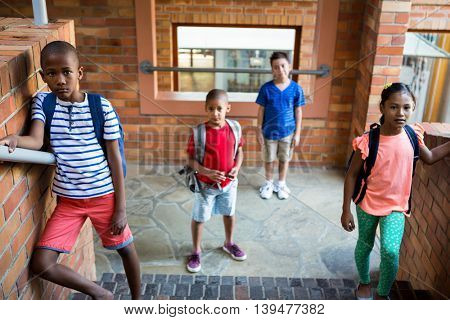 High angle view of classmates standing at school corridor