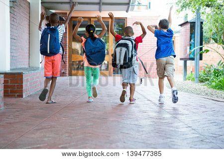 Rear view of playful classmates running at school corridor