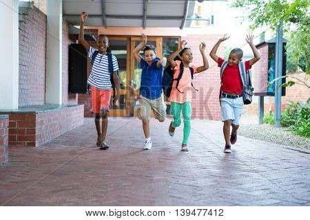 Playful classmates running at school corridor