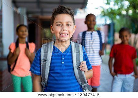 Portrait of happy schoolboy with classmates in background at school corridor