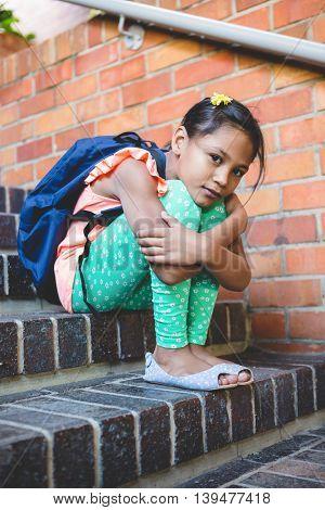 Portrait of girl sitting on steps at corridor in school