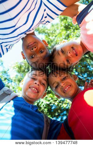 Low angle portrait of happy children forming huddle at park