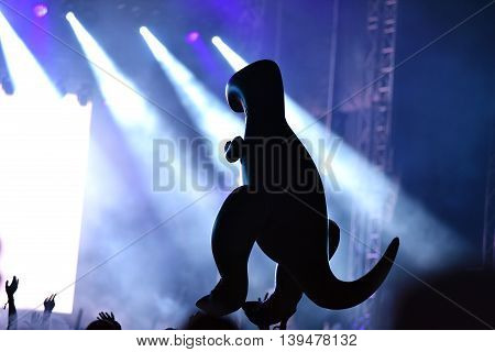 Silhouette Of An Inflatable Dinosaur At A Live Concert. Stage Lights In The Background