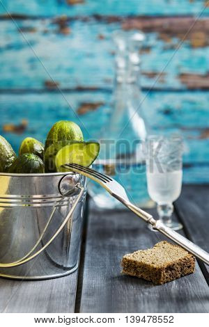 Pickled cucumbers in a zinc bucket on a dark wooden background with a decanter of vodka, a glass and black bread