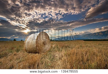 Sunset over farm field with hay bales.