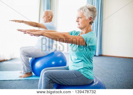 Seniors using exercise ball in a studio