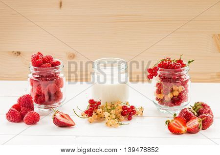 yogurt and berry in glass jars on white table at wooden background