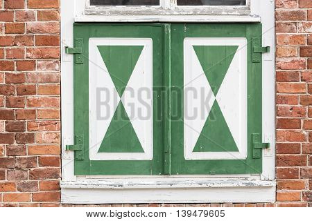 Closed window of an old brick house, dutch style
